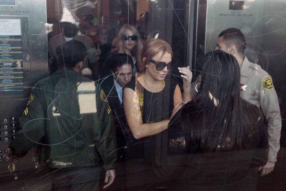 . Lindsay Lohan is escorted by Los Angeles County Sheriffs as she arrives in court for a pretrial hearing in a case filed over the actress\' June car crash in Los Angeles Wednesday, Jan. 30, 2013. Lohan faces three misdemeanor charges, and a return to jail, if convicted in the case or if a judge finds she violated her probation.(AP Photo/Damian Dovarganes)