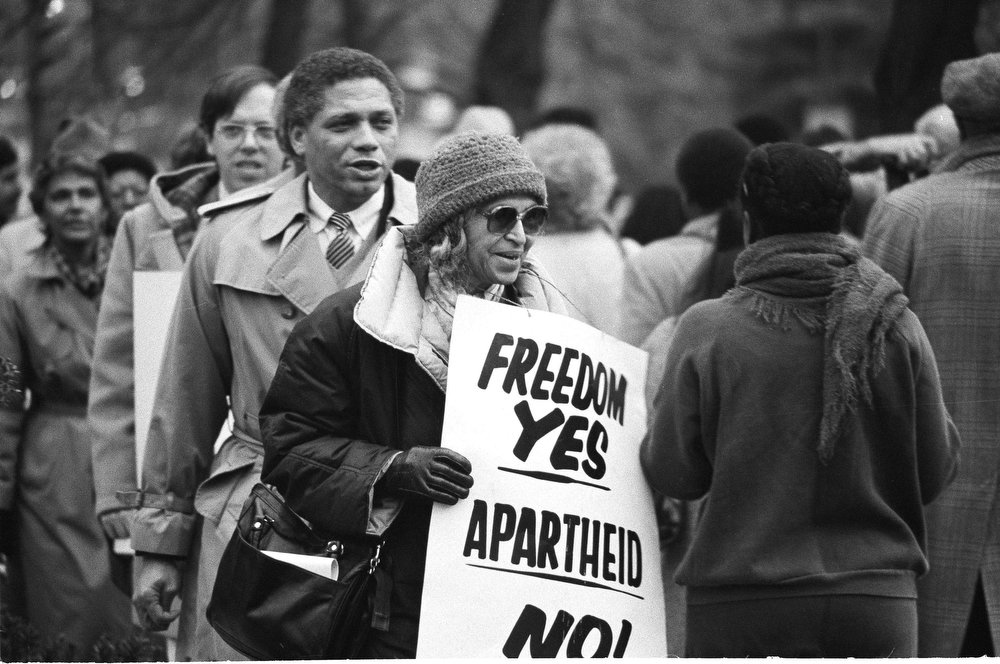 Description of . Rosa Parks, who sparked the civil rights movement nearly 30 years ago by refusing to give up a bus seat in Montgomery, Ala., joins in a march at the South African Embassy in Washington, Dec. 10, 1984, protesting that country's racial policies.  Rep. Mickey Leland, D-Tex., marches behind her.  (AP Photo)