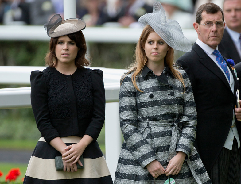 . Princess Beatrice, right, and sister Eugenie stand during the minuets silence for race horse trainer Henry Cecil who died recently, on the first day of the Royal Ascot horse race meeting in Ascot, England, Tuesday, June 18, 2013. (AP Photo/Alastair Grant)