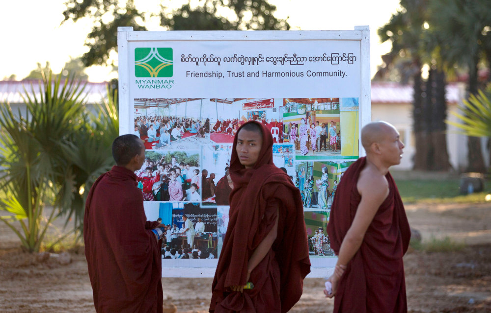 Description of . Buddhist monks read a promotional billboard of the Chinese mine company Wan Bao Co. Ltd. during a protest in Letpadaung mine, Monywa township, northwestern Myanmar, Wednesday, Nov. 28, 2012. Hundreds of Buddhist monks and villagers occupying the mine, they said is causing environmental, social and health problems, defied a government order to leave by Wednesday, saying they will stay until the project is halted. (AP Photo/Gemunu Amarasinghe)