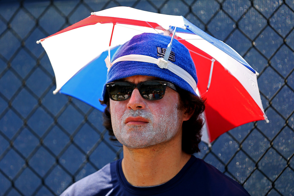 . NEW YORK, NY - AUGUST 27:  A spectator uses an umbrella hat to shelter from the sun during Day Two of the 2013 US Open at USTA Billie Jean King National Tennis Center on August 27, 2013 in the Flushing neighborhood of the Queens borough of New York City.  (Photo by Matthew Stockman/Getty Images)