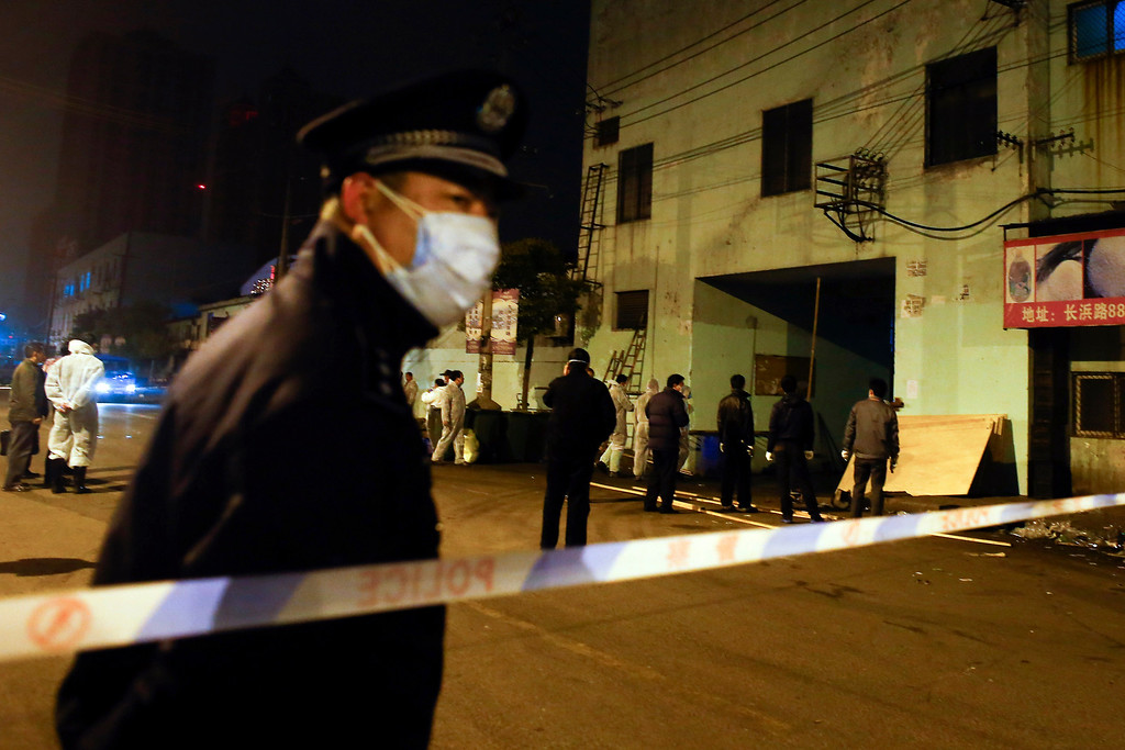 . A Chinese policeman wears a mask as he guards an access to a wholesale market where authorities are culling poultry after the new bird flu strain was detected there in pigeons being sold for meat in Shanghai on Friday April 5, 2013. China announced a sixth death from a new bird flu strain Friday, while authorities carried out the slaughter of all poultry at a Shanghai market where the virus was detected in pigeons being sold for meat. (AP Photo)