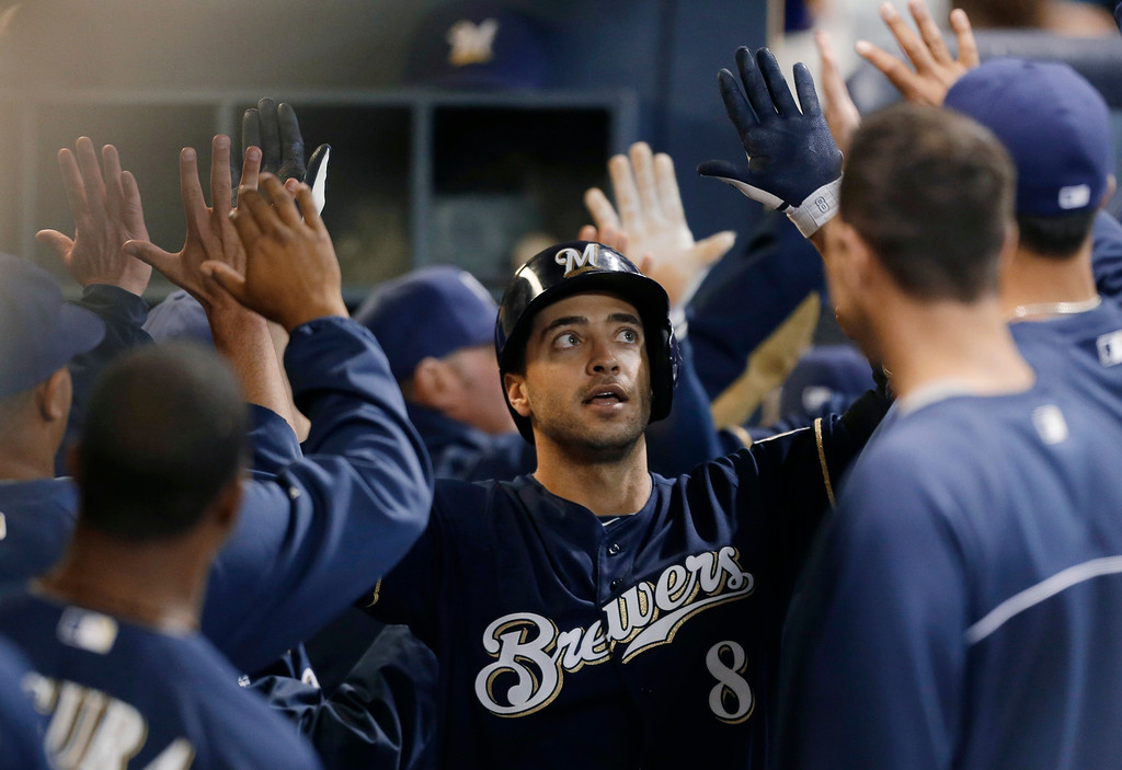 . Milwaukee Brewers\' Ryan Braun (8) gets high-fives in the dugout after his two-run home run against the Colorado Rockies during the third inning of a baseball game Tuesday, April 2, 2013, in Milwaukee. (AP Photo/Jeffrey Phelps)