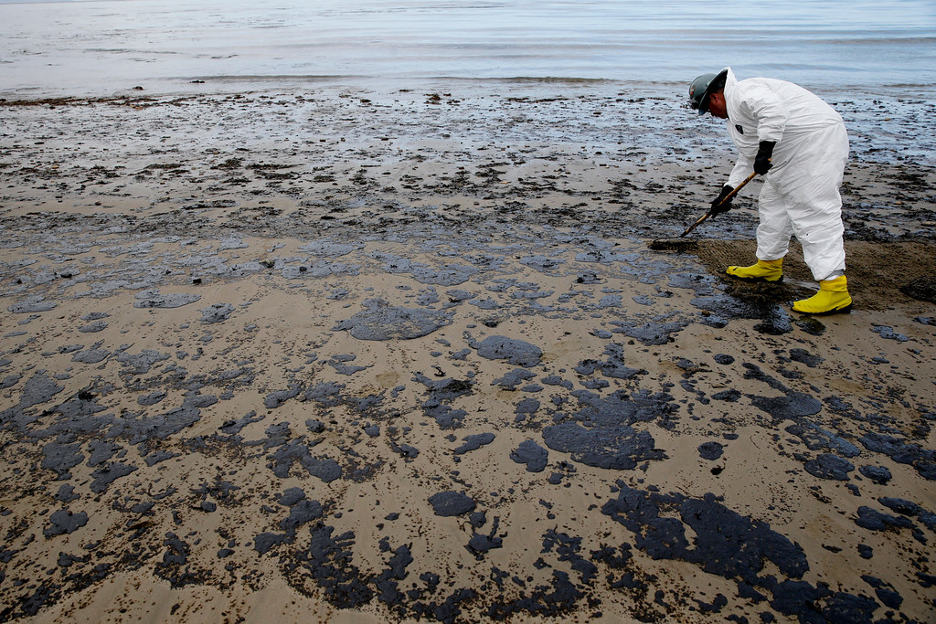 . A worker removes oil from the beach at Refugio State Beach, north of Goleta, Calif., Thursday, May 21, 2015. More than 7,700 gallons of oil has been raked, skimmed and vacuumed from a spill that stretched across 9 miles of California coast, just a fraction of the sticky, stinking goo that escaped from a broken pipeline, officials said. (AP Photo/Jae C. Hong)