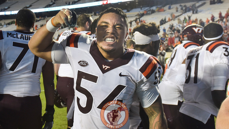 Virginia Tech linebacker Andrew Motuapuaka (54) celebrates with a piece of the carolina blue turf. (Michael Shroyer/ TheKeyPlay.com)