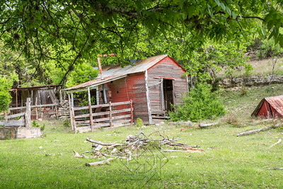 Abandon red shack in field with broken fence