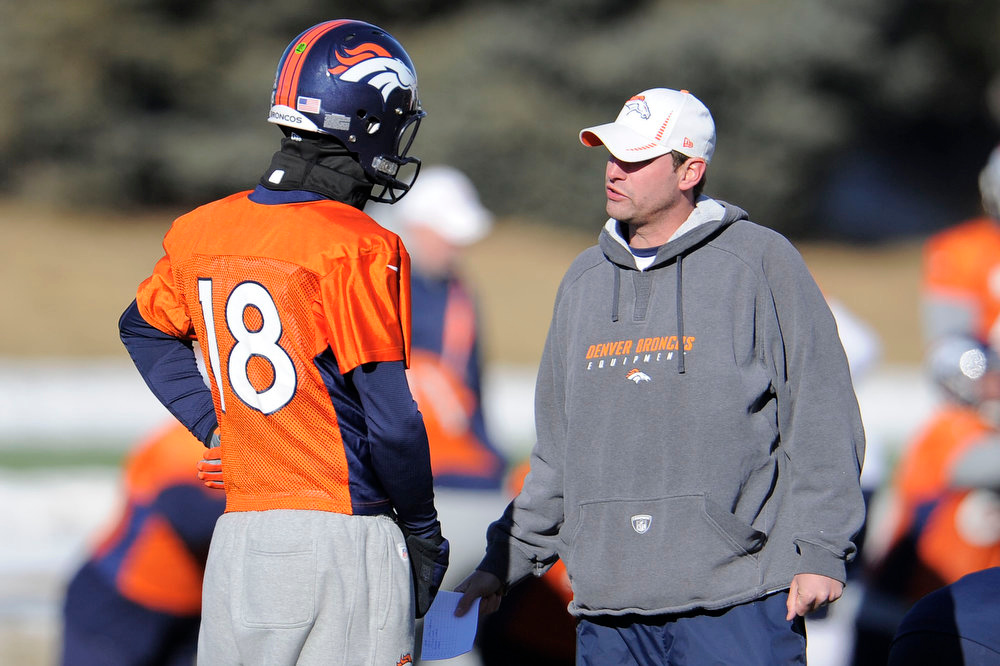 . Denver Broncos quarterback Peyton Manning (18) talks with quarterbacks coach Adam Gase during practice Wednesday, January 2, 2013 at Dove Valley.  John Leyba, The Denver Post
