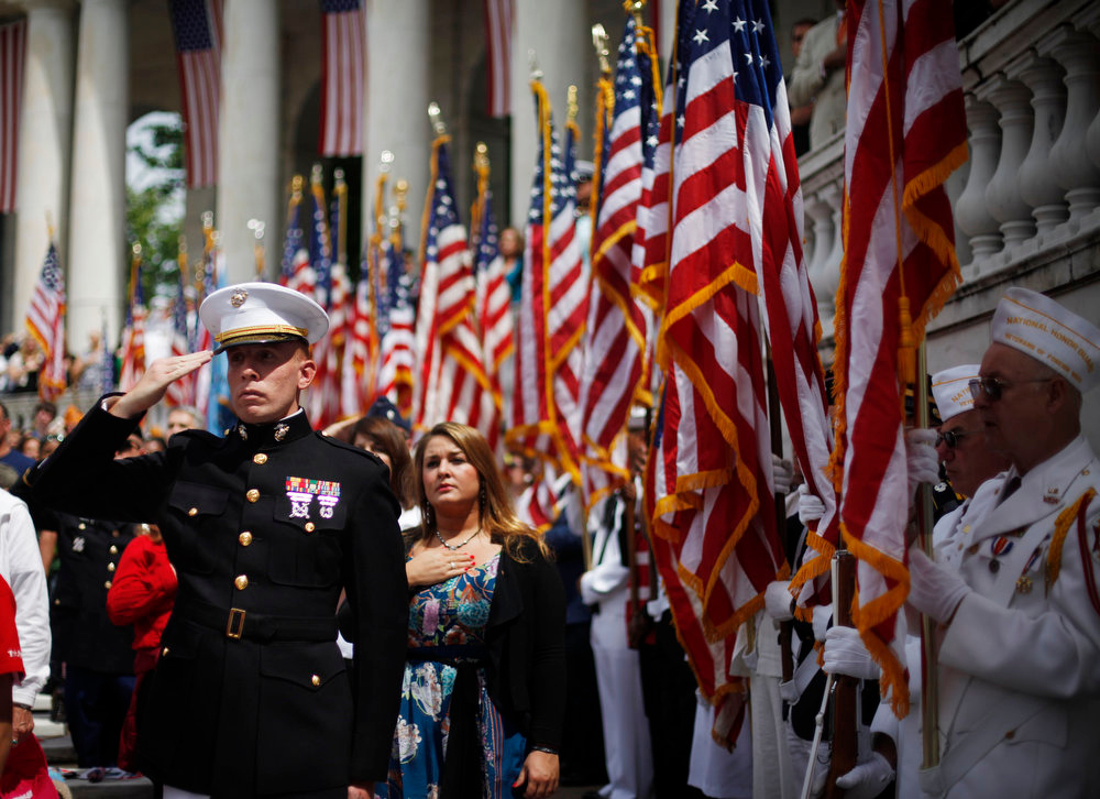 . U.S. Marine Corps, 2nd Lt. Adam Carroll, left, pays tribute as he salutes during the playing of the National Anthem at the Memorial Day ceremony in the Memorial Amphitheater at Arlington National Cemetery Monday, May 27, 2013, in Arlington, Va. (AP Photo/Pablo Martinez Monsivais)