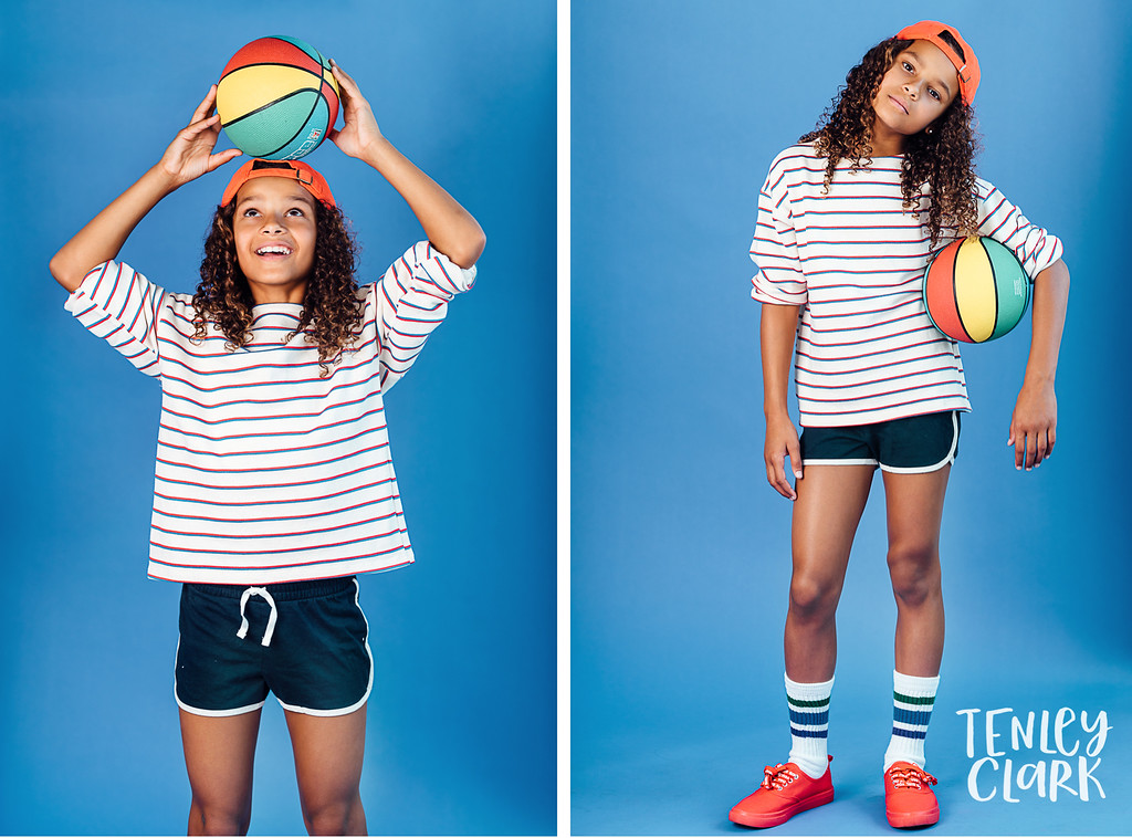 Playful, colorful studio kids headshots by Tenley Clark Photography. Sisters in retro basketball looks.