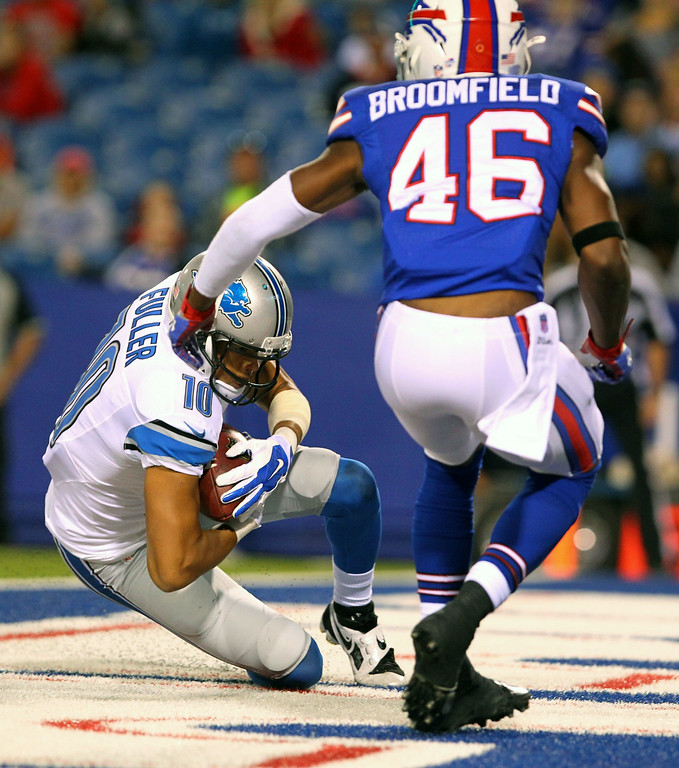 . Detroit Lions wide receiver Corey Fuller (10) drops in front of Buffalo Bills defensive back Deon Broomfield (46) while making a touchdown catch on a pass from quarterback Kellen Moore during the first half of a preseason NFL football game, Thursday, Aug. 28, 2014, in Orchard Park, N.Y. (AP Photo/Bill Wippert)