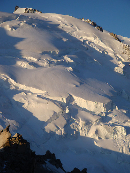 Slab avalanches occassionally break off Mt Blanc du Tacul, sweeping the face clean of climbers and other detruitus. That's partly why climbers prefer to pass such regions before the dawn sun hits them, whilst everything is still frozen solid.