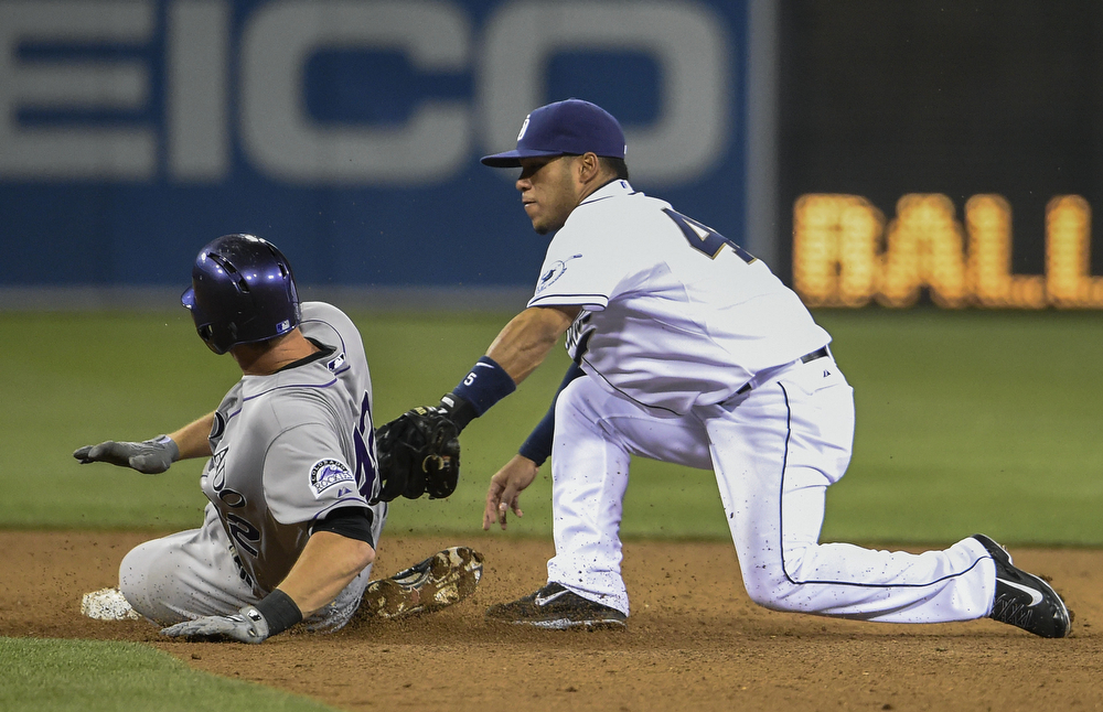 . SAN DIEGO, CA - APRIL 15:  Alexi Amarista of the San Diego Padres tags out DJ LeMahieu of the Colorado Rockies as he slides into second base during the sixth inning of a  baseball game at Petco Park April 15, 2014 in San Diego, California. All uniformed team members are wearing jersey number 42 in honor of Jackie Robinson Day. (Photo by Denis Poroy/Getty Images)