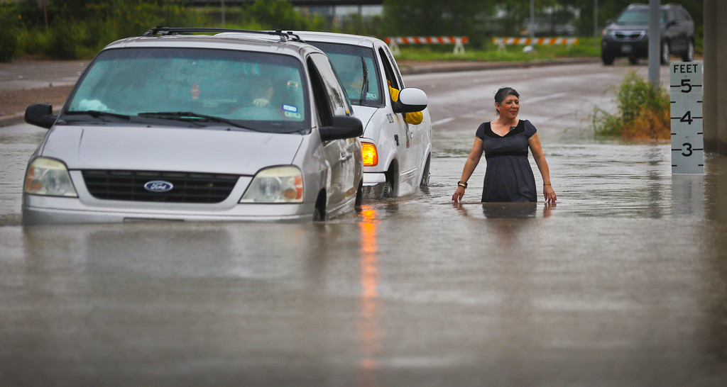 . A City of Brownsville vehicle pushes a stranded van that attempted to make it through the high waters along Mexico Boulevard in Brownsville, Texas, Thursday, May 28, 2015. Driving around the barriers and warning signs indicating high waters her attempt to make it through the waters failed.  (Yvette Vela/The Brownsville Herald via AP)