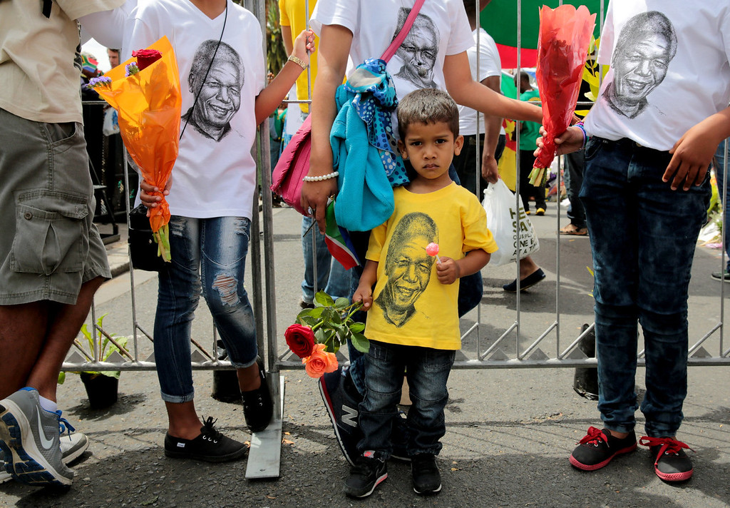 . A young boy watches the funeral of former South African president Nelson Mandela on big screens installed in front of the Cape Town City Hall, South Africa, Sunday, Dec. 15, 2013.  (AP Photo/Nardus Engelbrecht)