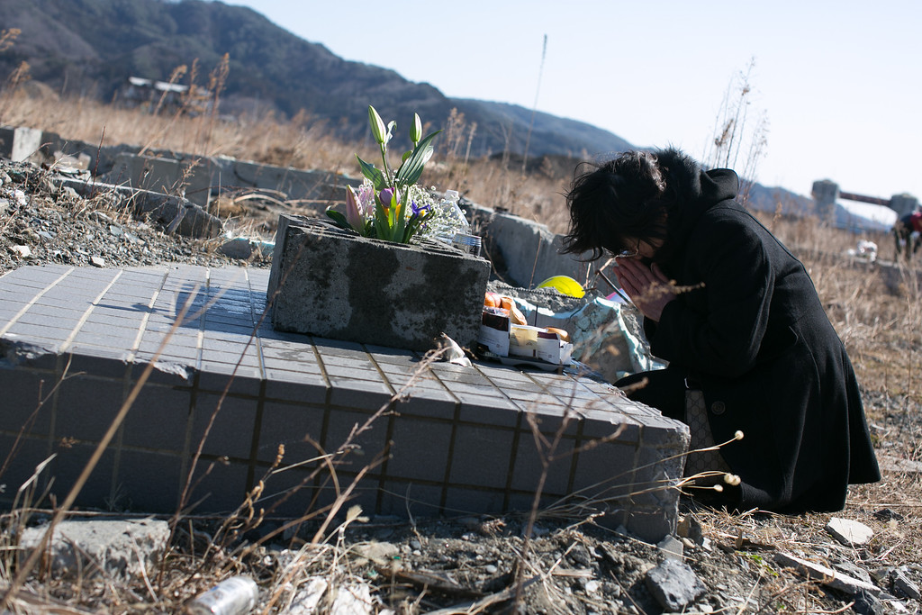 . A women prays for her family where her house used to stand on March 11, 2013 in Ootsuti, Iwate prefecture, Japan.  On March 11 Japan commemorates the second anniversary of the magnitude 9.0 earthquake and tsunami that claimed more than 18,000 lives.  (Photo by Ken Ishii/Getty Images)