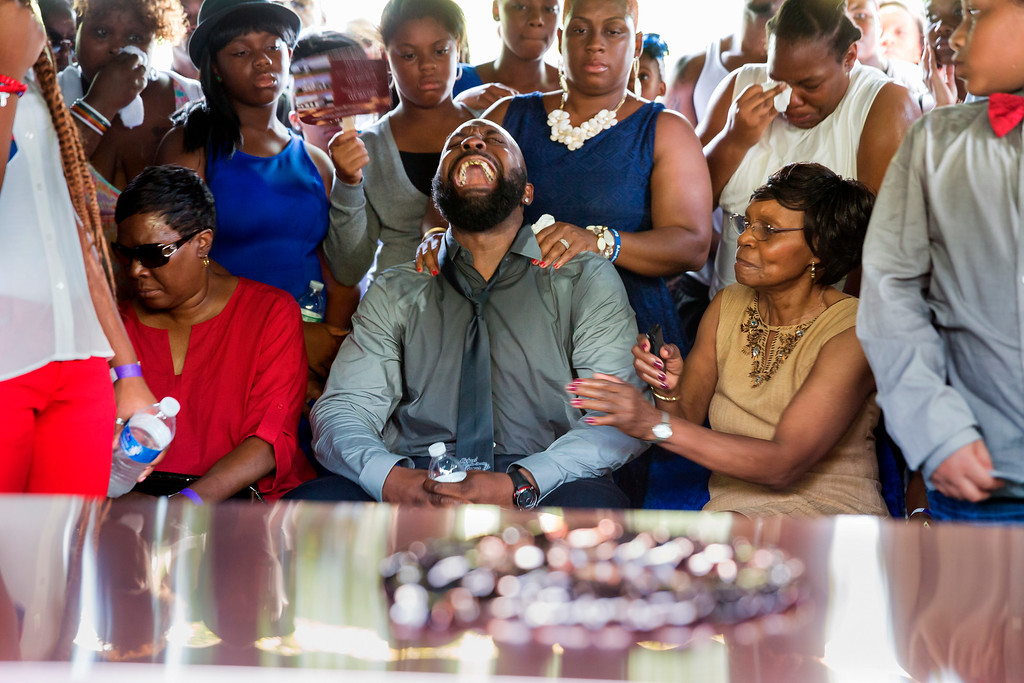 . Michael Brown Sr. yells out as the casket is lowered during the funeral service for his son Michael Brown in Normandy, Mo., Monday, Aug. 25, 2014. Hundreds of people gathered to say goodbye to Michael Brown, the 18-year-old shot and killed Aug. 9 in a confrontation with a police officer that fueled almost two weeks of street protests. (AP Photo/New York Times, Richard Perry, File Pool)
