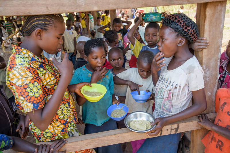 Marie Ngalula, 14, (with crocheted hair cover on) eats nutritious porridge at the Child Friendly Space near her home in Kasia Central Province.  Marie lives with her father, Alexandre Tshimanga, her mother, Ntumba Kalombo Antoinette and her brothers and sisters: 1-Kena Tshimanga, 12 2-Kankonde Moise, 10 3-Munamba Angel, 8 4-Musungayi Andre, 6 5-Mubuyi Tshimanga, 4  Marie lives in a small village outside of Kananga, Democratic Republic of Congo, DRC, called Tubuluku, which means antelopes (plural). Her house is a two-room hut with a thatched roof.  Handful of wooden chairs are the only furniture. She lives here with an extended family of 13.  Home Life Marie is a bright girl but there is a sadness in her eyes. Marie's mother is in the nearby health clinic with a staph infection that has caused a huge abscess on her right side. It has become very serious. As a result, Marie has assumed many of the household duties.  She's forced, at 14, to assume the duties of an adult. Besides cooking for her brothers and sisters, she sweeps up the husks from palm nuts she crushes. She saves the husks to use as kindling for the fire. Marie and her siblings all sleep together in one room, huddled together for warmth and cover by an old and torn mosquito net.  Hunger Marie's family is desperately hungry in the days we visit them. Because her mother is sick and his father spends his days tending to her in the clinic, there is no money for food. Because there isn't any cassava flour and cornmeal to make fufu, a bread-like dish that's a Congolese staple, Marie and her siblings pick potato leaves from the garden. Marie sharpens a knife on a rock and uses it to chop the leaves into small pieces. She holds a bunch tightly in her left hand and runs the knife through them.  Her cousin, also named Marie Ngalula, pulls some wood from a pile and arranges it between three rocks that will hold the pot. She yanks some thatch from the roof and uses it for kindling. Because they also have no oil or sa