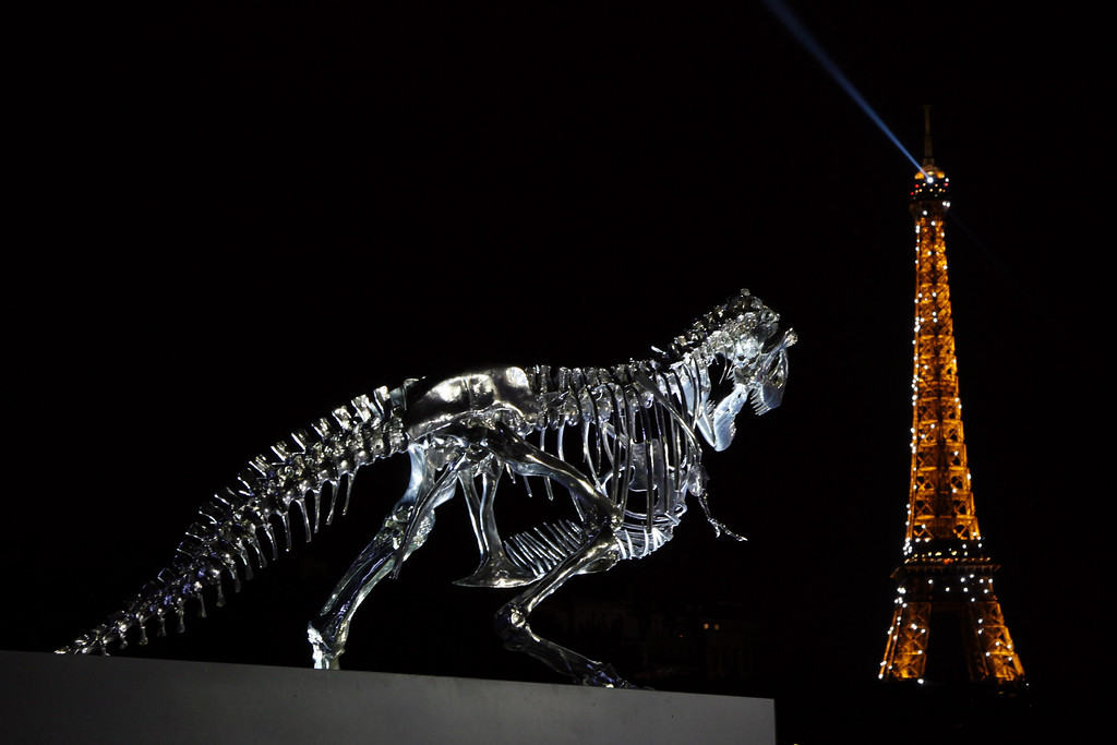 . A giant chrome brushed aluminium skeleton of a Tyrannosaurus (T-Rex) dinosaur (L), made by French sculptor and painter Philippe Pasqua, stands at the pier of riverboat company Bateaux-Mouches on June 12, 2013 in Paris, with the Eiffel tower in the background (R). (CLAIRE LEBERTRE/AFP/Getty Images)