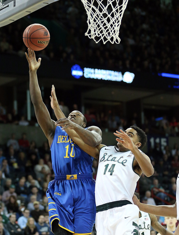 . Devon Saddler #10 of the Delaware Fightin Blue Hens shoots over Gary Harris #14 of the Michigan State Spartans during the second round of the 2014 NCAA Men\'s Basketball Tournament at Spokane Veterans Memorial Arena on March 20, 2014 in Spokane, Washington.  (Photo by Stephen Dunn/Getty Images)