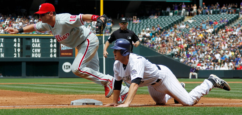 . Philadelphia Phillies third baseman Micahel Young, back, chases down an errant throw by catcher Humberto Quintero as Colorado Rockies\' DJ LMahieu dives safely back into third base in the first inning of a baseball game in Denver, Saturday, June 15, 2013. LeMahieu ended up scoring on the the throwing error by Quintero. (AP Photo/David Zalubowski)