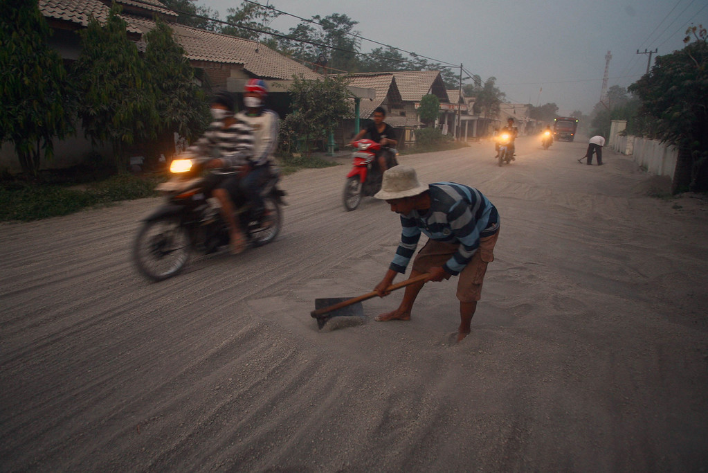 . A resident clears volcanic ash on the road of Kediri in East Java province following the eruption of Mount Kelud volcano on February 14, 2014.  AFP PHOTO / JUNI KRISWANTO/AFP/Getty Images