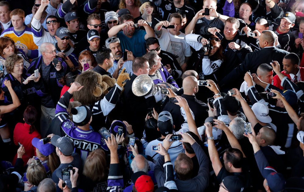 Description of . Los Angeles Kings fans cheer as they take pictures of the Stanley Cup outside the Staples Center before an NHL hockey game between the Los Angeles Kings and the Chicago Blackhawks in Los Angeles, Saturday, Jan. 19, 2013. (AP Photo/Jae C. Hong)