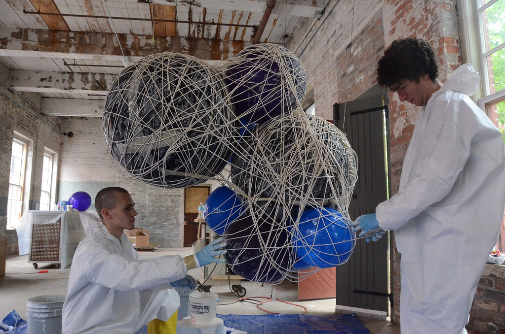 . Jackson Kleiser, left, assists Jeremy Roth, who does lighting visual production and design, with making string lamps or \'clouds\' that will hang over the stage during the Solid Sound weekend at Mass MoCA starting on Friday.(Gillian Jones/North Adams Transcript)