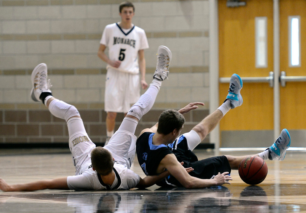 . LOUISVILLE, CO - JANUARY 3: Mountain Range\'s Tyler Sullivan (4) and Monarch\'s Ben Beauchamp (31) work to get control of a loose ball. Monarch High School boys basketball takes on Mountain Range High School at Monarch High School in Louisville. (Photo by Kathryn Scott Osler/The Denver Post)