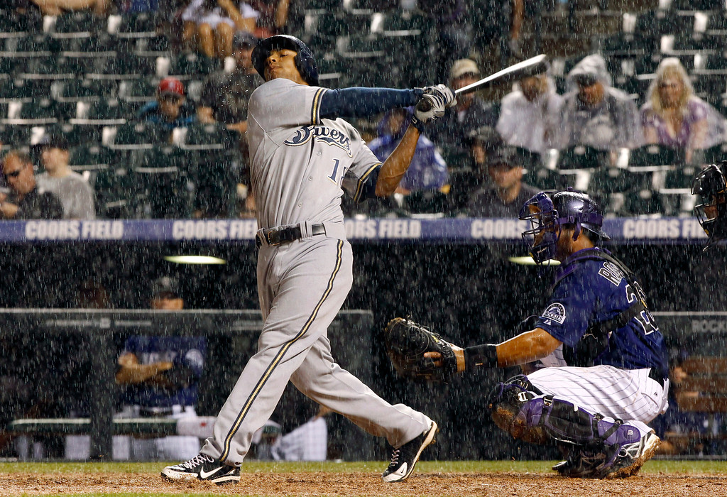 . Heavy rain falls on Milwaukee Brewers pinch-hitter Khris Davis as he singles while Colorado Rockies catcher Wilin Rosario looks on in the ninth inning of a baseball game in Denver on Saturday, July 27, 2013. Umpires halted play as the Rockies came to bat in the bottom of the ninth inning. (AP Photo/David Zalubowski)