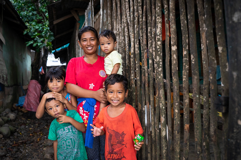 This is Maria and four of her five children. Her eldest daughter is away at school; Maria is hopeful the education provides her more financial stability. The family is posing in front of their Port Barton home. Located just off the water their home is quite simple — a single room that features a small outdoor kitchen and one cot for sleeping.