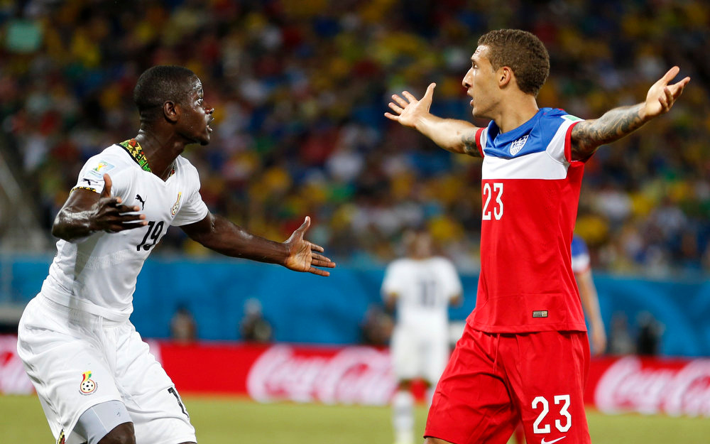 Description of . United States' Fabian Johnson, right, and Ghana's Jonathan Mensah question the referee's call during the group G World Cup soccer match between Ghana and the United States at the Arena das Dunas in Natal, Brazil, Monday, June 16, 2014. (AP Photo/Julio Cortez)