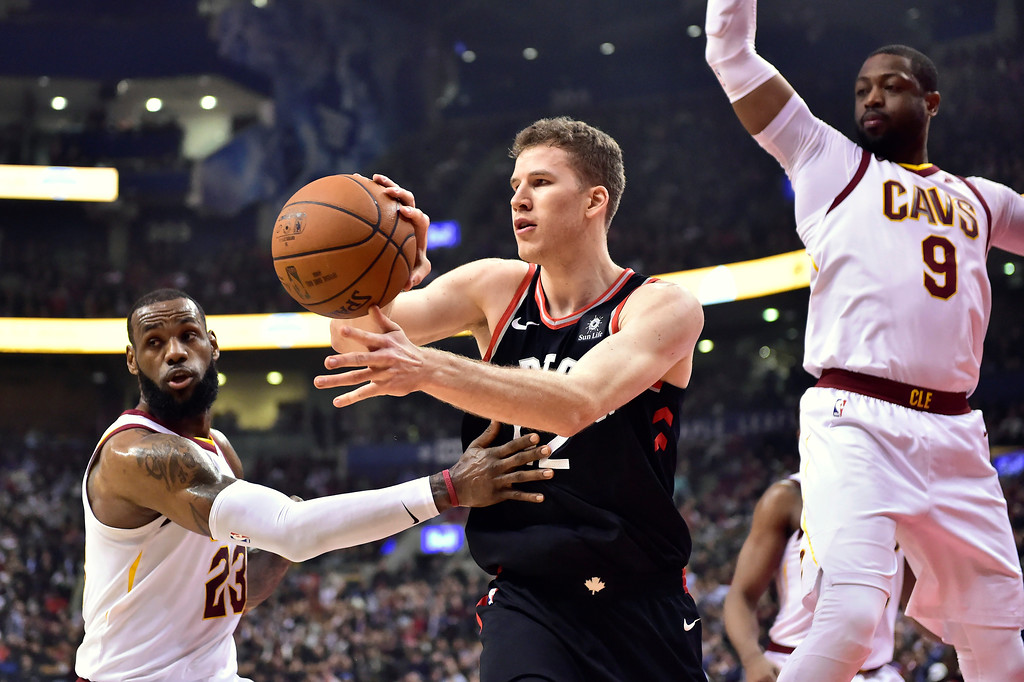 . Toronto Raptors center Jakob Poeltl (42) passes the ball as Cleveland Cavaliers forward LeBron James (23) and guard Dwyane Wade (9) defend during the first half of an NBA basketball game Thursday, Jan. 11, 2018, in Toronto. (Frank Gunn/The Canadian Press via AP)
