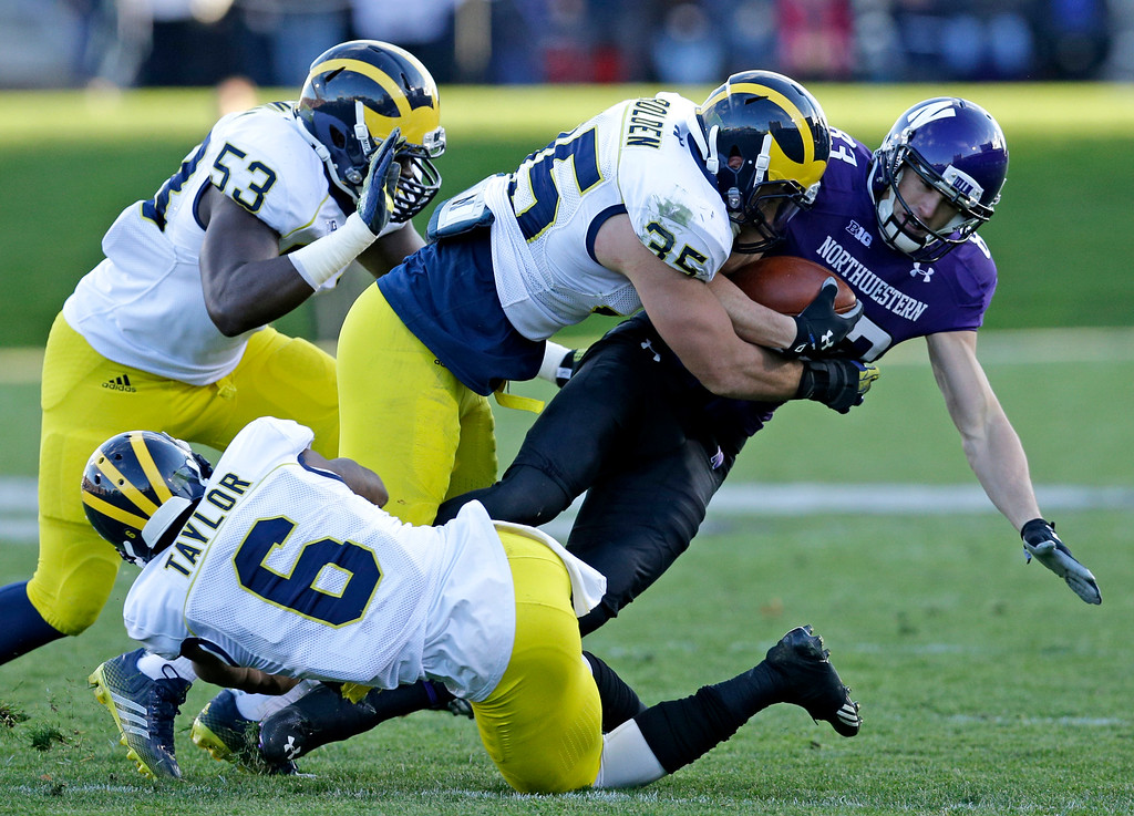 . Northwestern wide receiver Mike McHugh (83) is tackled by Michigan linebacker Joe Bolden (35), defensive end Mario Ojemudia (53) and defensive back Raymon Taylor (6) during the first half of an NCAA college football game in Evanston, Ill., Saturday, Nov. 8, 2014. Michigan won 10-9. (AP Photo/Nam Y. Huh)