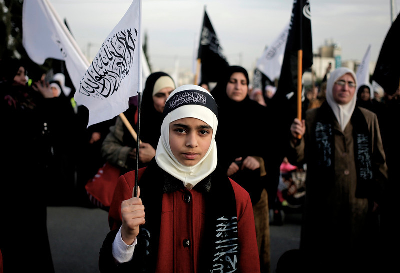 """. Women followers of the banned Islamic-oriented Hizb Al-Tahrir take part in a demonstration in front of the Syrian embassy to condemn the peace talks in Switzerland between the Syrian government and the opposition, in Amman, Jordan, Wednesday, Jan. 22, 2014. The white and black flags Arabic read \""""there is No God but Allah and Muhammad is his messenger.\"""" (AP Photo/Mohammad Hannon)"""