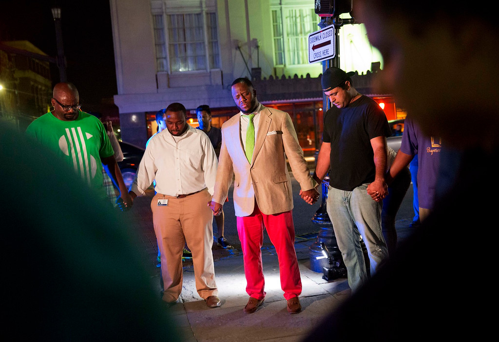 . Worshippers gather to pray down the street from the Emanuel AME Church following a shooting Wednesday, June 17, 2015, in Charleston, S.C. (AP Photo/David Goldman)