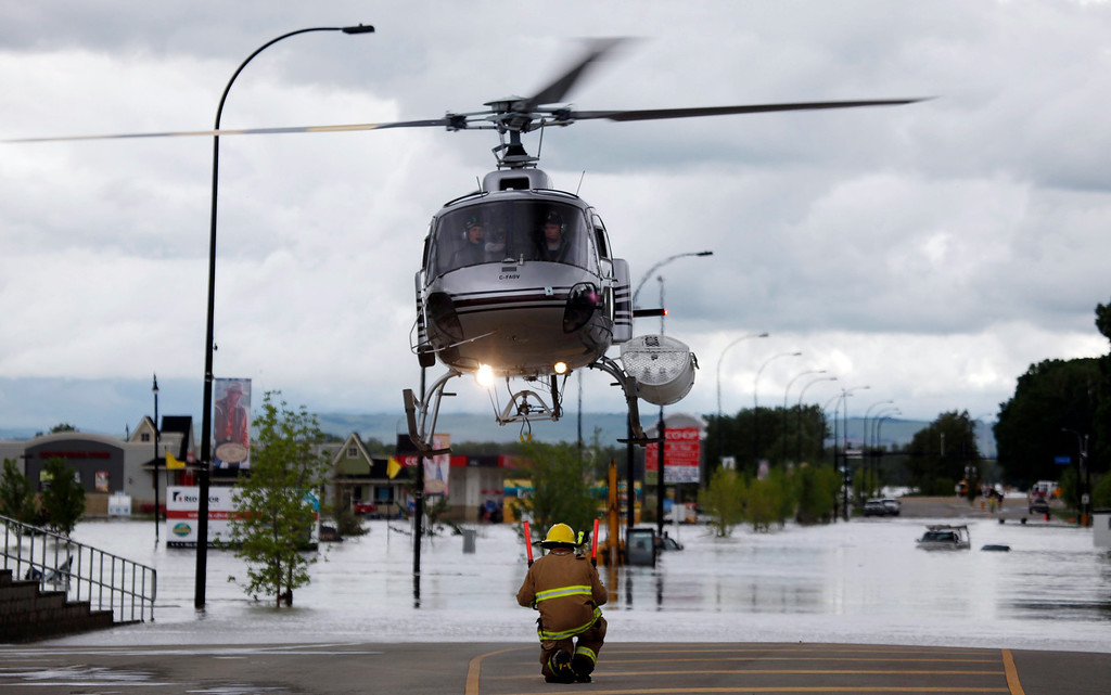 . A helicopter carrying evacuated residents lands on a road in High River, Alta., Thursday, June 20, 2013. Calgary city officials say as many as 100,000 people could be forced from their homes due to heavy flooding in western Canada, while mudslides have forced the closure of the Trans-Canada Highway around the mountain resort towns of Banff and Canmore. (AP Photo/The Canadian Press, Jeff McIntosh )