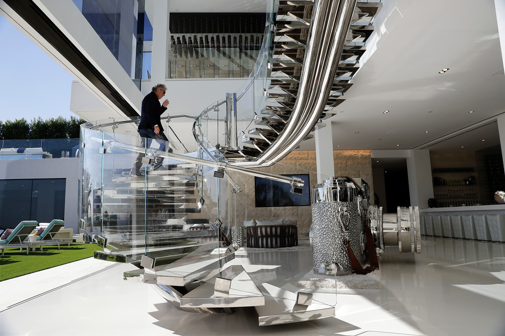. In this Thursday, Jan. 26, 2017, photo, developer Bruce Makowsky walks up the handcrafted steel staircase next to a large sculpture of a Leica camera at a $250 million mansion he built in the Bel-Air area of Los Angeles. The mansion includes 12 bedroom suites, 21 bathrooms, five bars, three gourmet kitchens, a spa and an 85-foot infinity swimming pool with stunning views of Los Angeles. (AP Photo/Jae C. Hong)