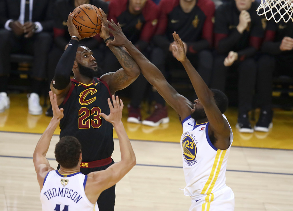 . Cleveland Cavaliers forward LeBron James, top left, shoots against Golden State Warriors guard Klay Thompson, bottom left, and forward Draymond Green during the first half of Game 1 of basketball\'s NBA Finals in Oakland, Calif., Thursday, May 31, 2018. (AP Photo/Ben Margot)