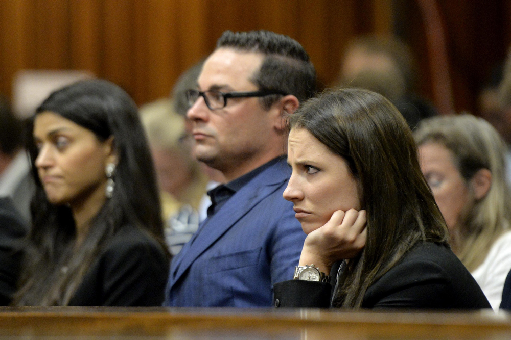 . Carl (C) and Aimee Pistorius (R), brother and sister of South African Paralympian star Oscar Pistorius, listen to the first witnesses during the opening day of the trial of Oscar Pistorius, accused of murdering his girlfriend Reeva Steenkamp, at the High Court in Pretoria on March 3, 2014. Pistorius, 27, appeared in court and on television screens around the world to answer charges that he willfully shot his girlfriend Reeva Steenkamp dead on Valentine\'s Day 2013 through a locked bathroom door at his home in the city, and faces a life sentence if convicted. (HERMAN VERWEY/AFP/Getty Images)