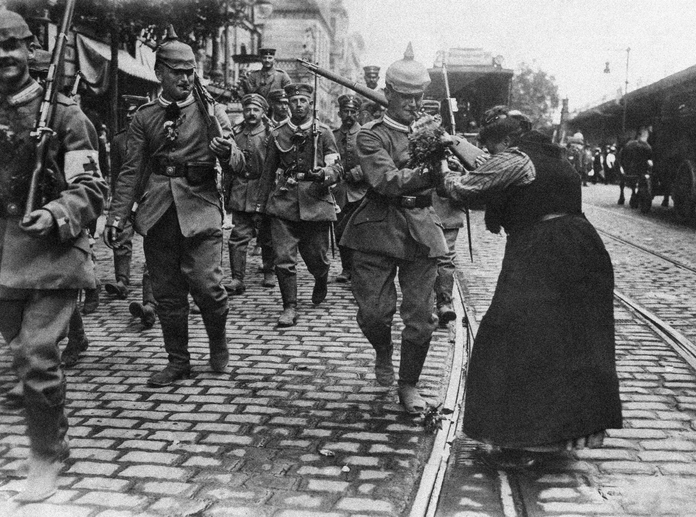 Description of . Prussian guard infantry in New Field gray uniforms leave Berlin, Germany to entrain for the front, August 1914 during World War I. Girls and women along the line of march and out flowers to them. (AP Photo)