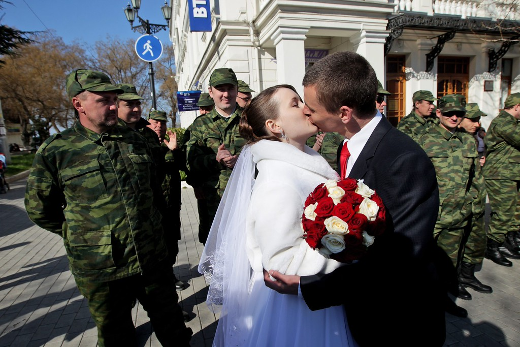 . Members of a pro-Russian self defense unit watch and applaud as a groom and a bride share a kiss at the central square of Sevastopol, Crimea, Ukraine 15 March 2014.   EPA/ZURAB KURTSIKIDZE