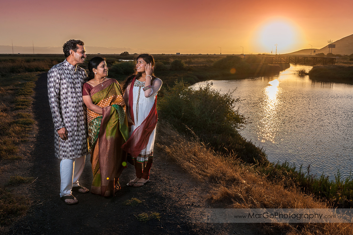 Indian family walking along the water during sunset at Don Edwards Refuge in Fremont
