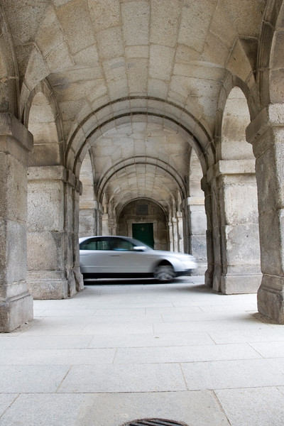Contrasting image of a car through an old arcade