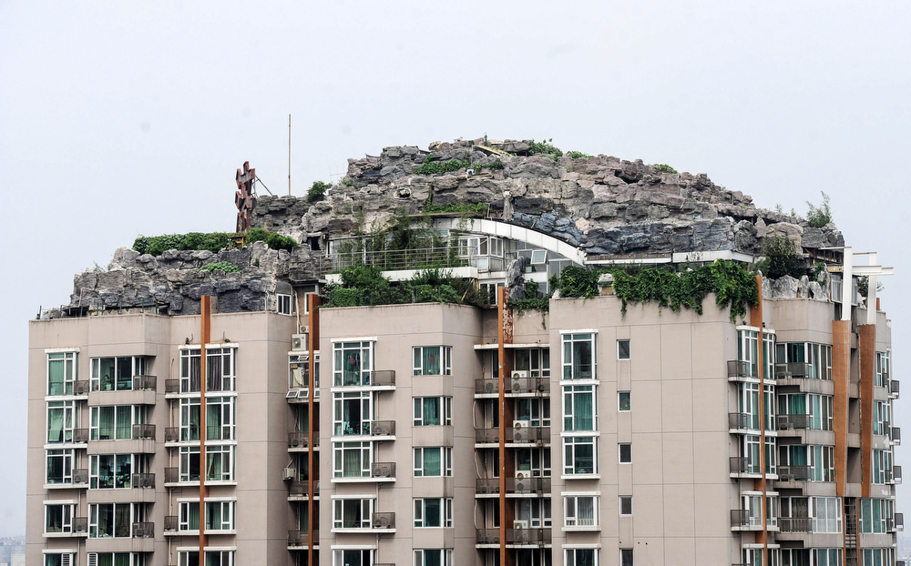 . This Aug. 12, 2013 photo released by China\'s Xinhua News Agency shows a residential building with a rocky style villa on its roof, in Haidian District of Beijing, China. Beijing authorities are planning to demolish the bizarre rooftop villa embedded in rocks, trees and bushes that allegedly was built illegally atop a 26-story apartment block in the capital. (AP Photo/Xinhua, Luo Xiaoguang)