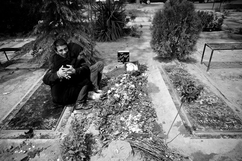 . Sara and Hossein hug each other over the grave of their mother Soheila Mehri during her burial ceremony at Behesht-e Zahra cemetery in Tehran on April 14, 2013, a day after she died.  Soheila, a retired primary school teacher in Iran, passed away at the age of 54 after battling breast cancer for several months.  AFP PHOTO/BEHROUZ MEHRI