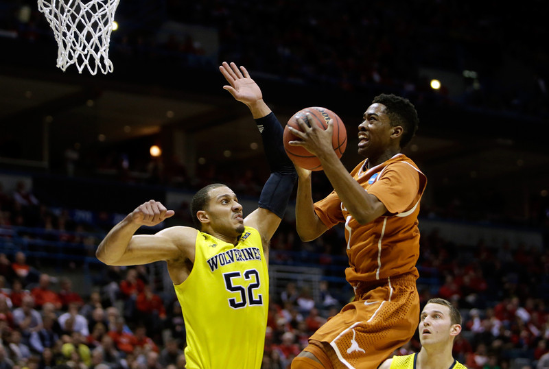 . Isaiah Taylor #1 of the Texas Longhorns drives to the basket against Jordan Morgan #52 of the Michigan Wolverines during the third round of the 2014 NCAA Men\'s Basketball Tournament at BMO Harris Bradley Center on March 22, 2014 in Milwaukee, Wisconsin.  (Photo by Mike McGinnis/Getty Images)
