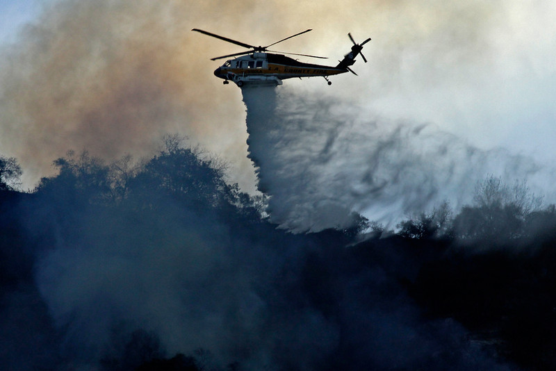 . A firefighting helicopter makes a water drop on the Colby Fire burning for a second day in the hillside above Highway 39 in Azusa, California, January 17. Three men have been arrested and charged with starting the fire that has now destroyed 1,700 acres of land and several homes around Glendora and Azusa in the San Gabriel Valley, prompting officials to order evacuations for houses near the fire. (Photo by Jonathan Alcorn/Getty Images)