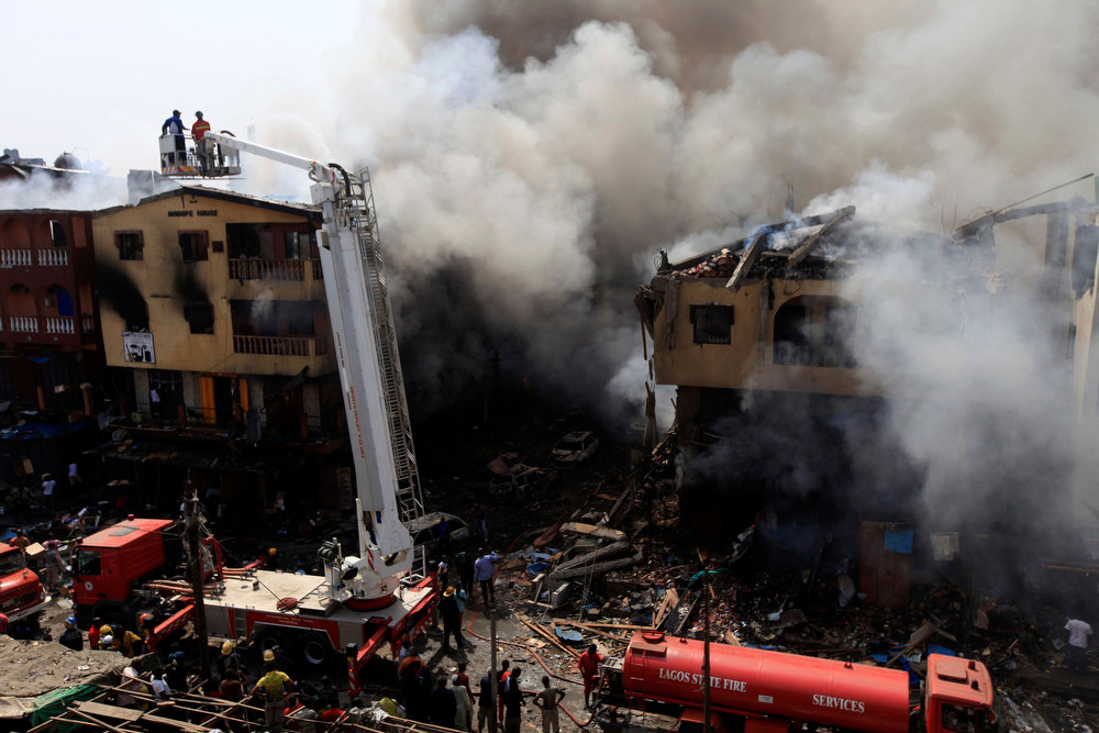 Description of . Firefighters use a crane to try extinguish a fire after fireworks stored in a building exploded in a densely populated area in the Isale Eko district in Nigeria\'s commercial capital of Lagos December 26, 2012. REUTERS/Akintunde Akinleye