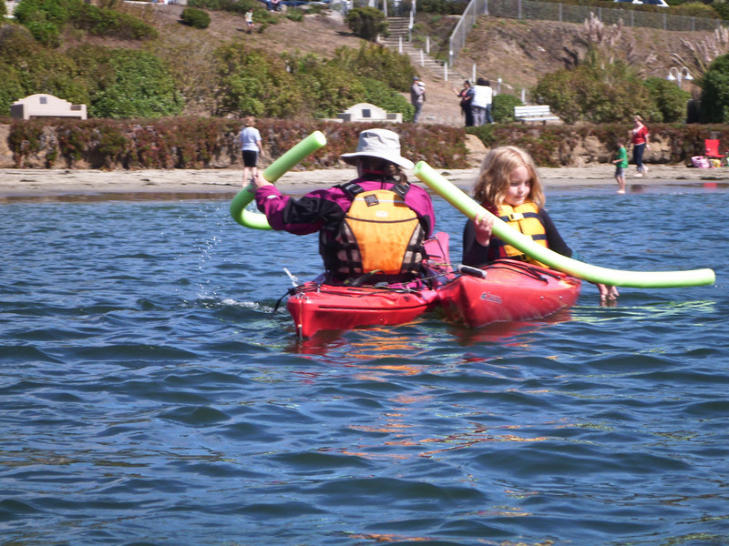 The next game was a race of two kayaks linked together and paddled using only swim noodles.    Helena and Hanna are working at it.
