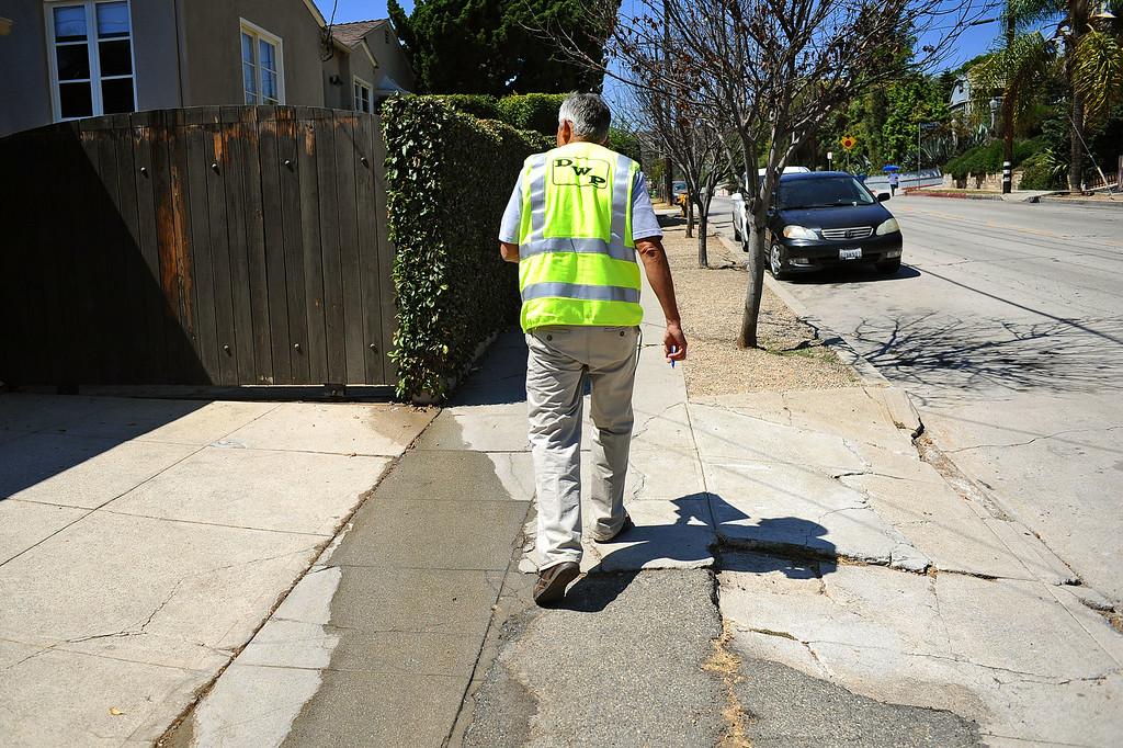 . Rick Silva of the DWP�s Water Conservation Response Unit investigates water runnning down a sidewalk while on patrol  Wednesday July 17, 2014.  Silva is in charge of monitoring water violations in LADWP\'s service area of just under 500 square miles. (Andy Holzman/Los Angeles Daily News)